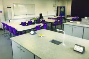 Modern science lab with Velstone work tops and a purple feature wall to create a design lead space.