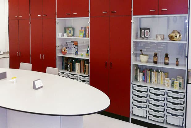 Teaching wall space with display cabinet with grey trays and red storage cupboards.